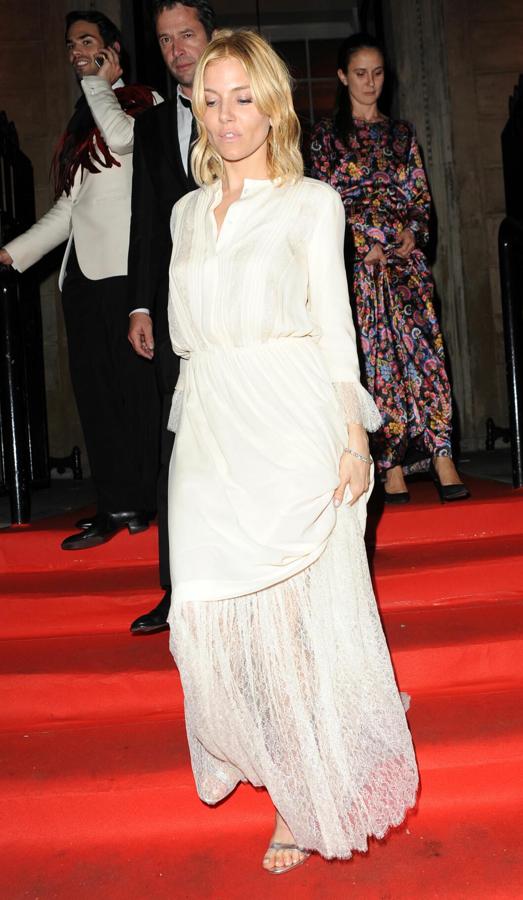YNDIG: Skuespiller Sienna Miller droppet tilsynelatende masken på VIP-festen, til fordel for en hvit blondekjole og sølvsko. Foto: Xposure