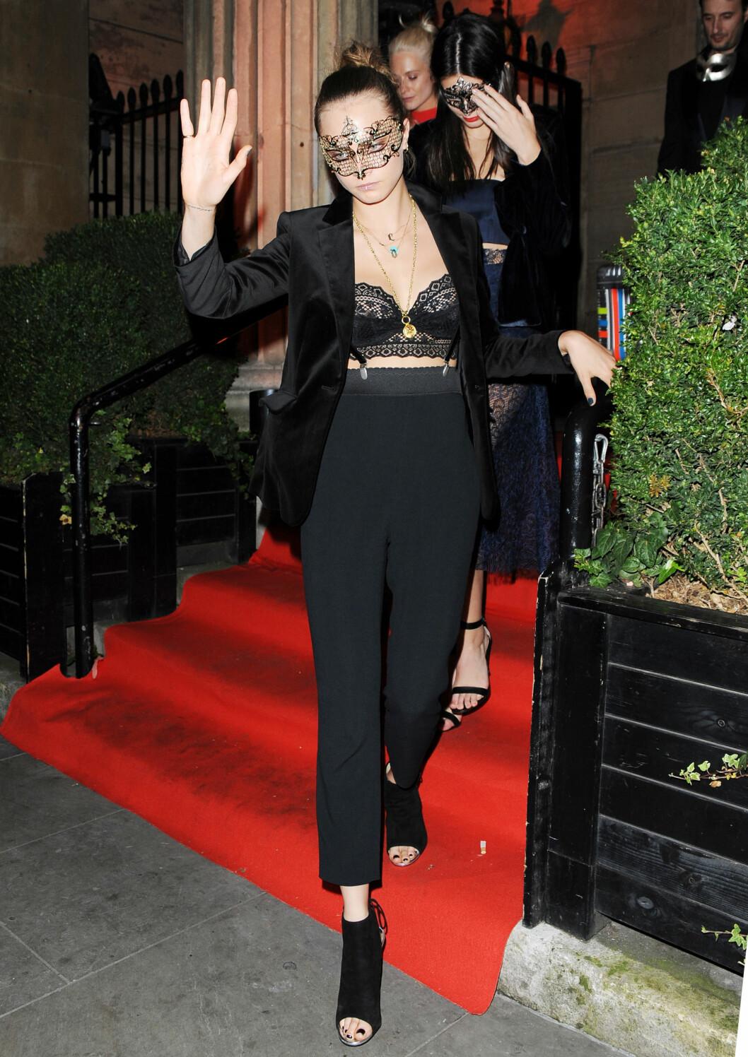 ROCKA: Modell og skuespiller Cara Delevingne stylet den lille BH-toppen sin med blazer, sort neglelakk og bukser med høyt liv og bukseseler. Legg merke til den forseggjorte masken i gull!  Foto: Xposure