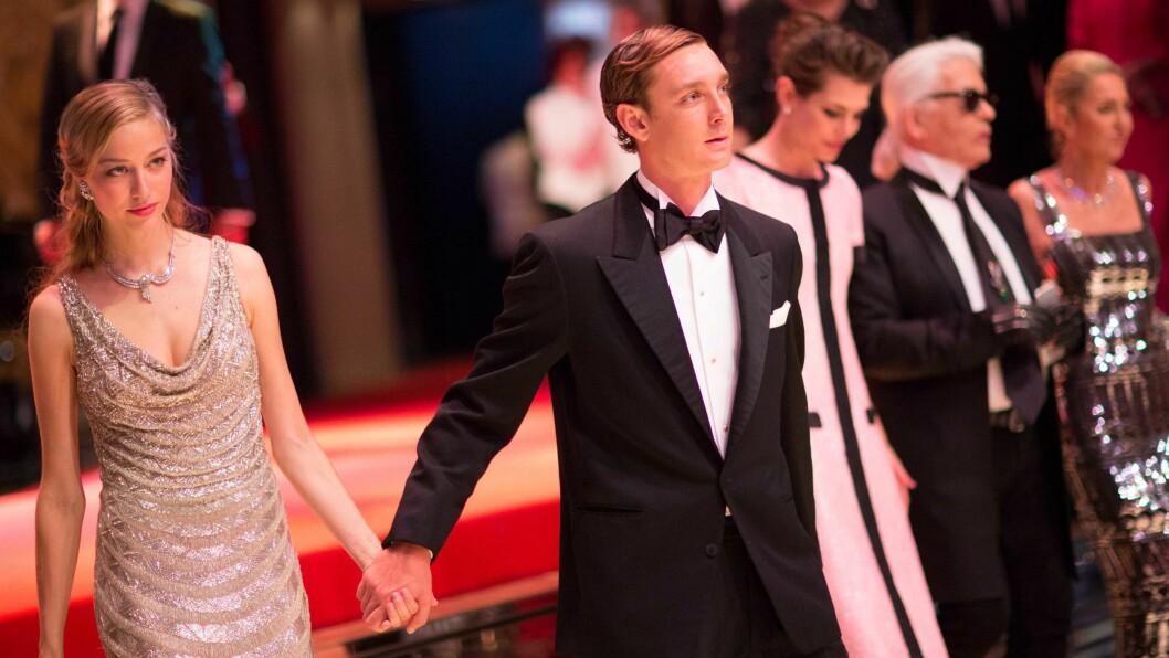 ROSA PÅ BALL: Under det årlige Rose-ballet i Monaco i mars i år, bar Beatrice Borromeo en lekker Valentino-kreasjon. Under bryllupet i helgen gikk hun for en spesialdesignet kjole fra det italienske motehuset. Her hånd i hånd med Pierre Casiraghi - som hun giftet seg med forrige helg. I bakgrunnen: svigerinnen Charlotte Casiraghi og den kjente motedesigneren Karl Lagerfeld. Foto: NTB Scanpix