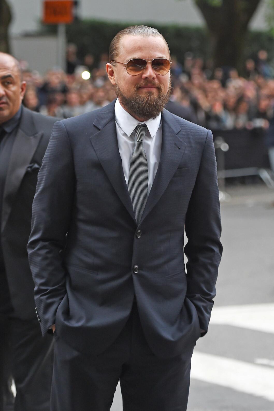 MYSTISK: Leonardo DiCaprio har den siste tiden sverget til «man bun» i nakken og langt skjegg. Her på 40-årsfeiringen av Giorgio Armani i Milano i april. Foto: Splash News