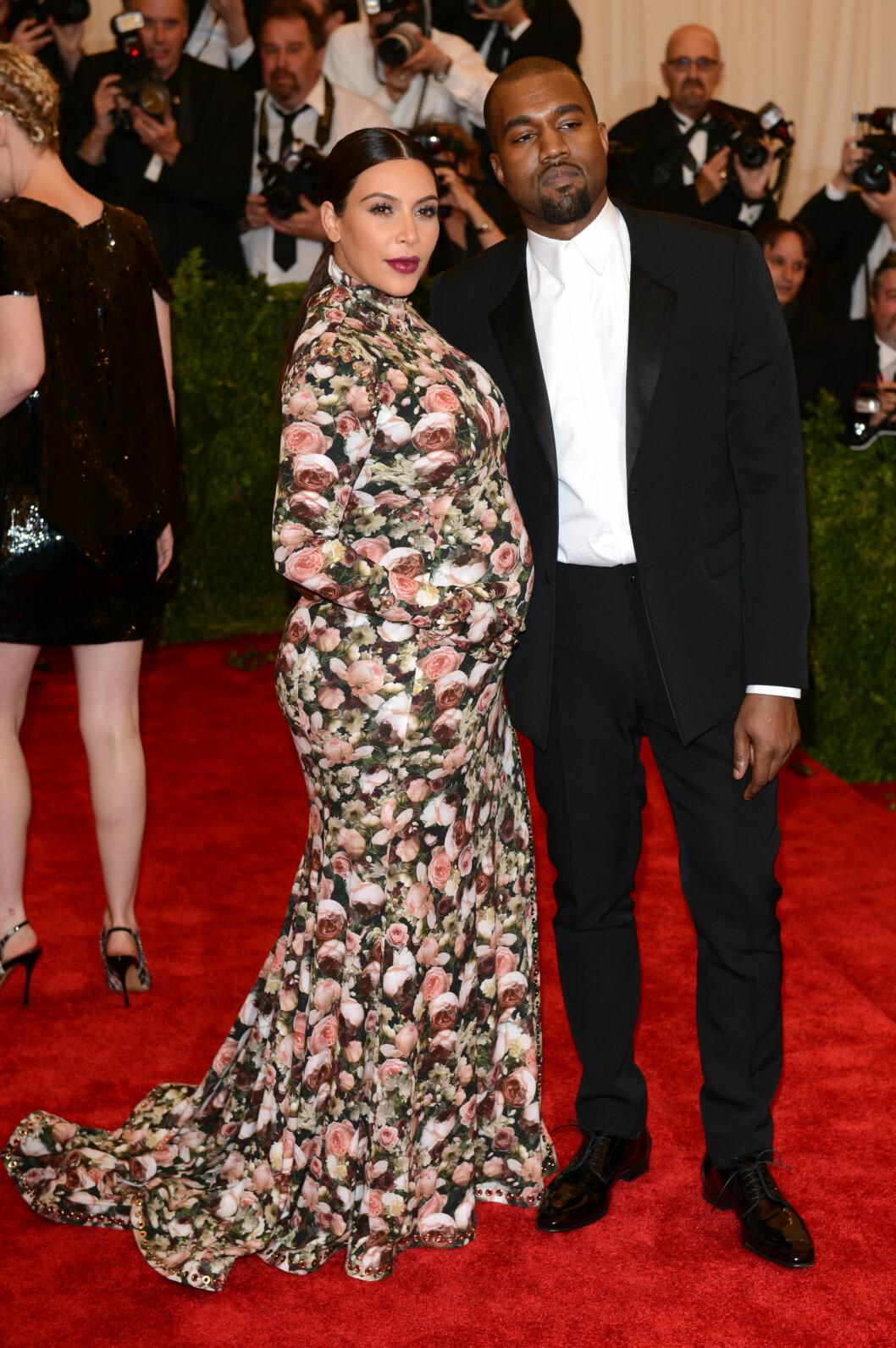 MED PÅ MOTENE: Dette bildet er tatt fem uker før Kim Kardashian fødte datteren North West i juni 2013. Under den årlige The Met Gala i New York i mai det året bar hun en spesialdesignet blomstrete kjole fra favorittmerket Givenchy. Her med ektemannen Kanye West. Foto: NTB Scanpix