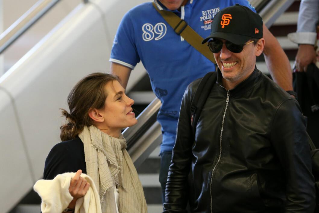 FORNØYDE MED FERIEN?: Charlotte Casiraghi og Gad Elmaleh ankommer flyplassen Orly i Paris sammen, søndag 7. juni. De to virket i svært godt humør. Foto: Abaca