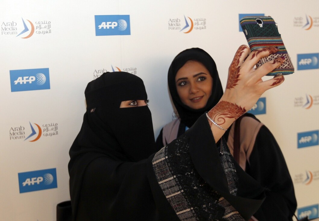 IKKE PÅBUDT: Særlig i Midtøsten bruker mange muslimske kvinner niqab grunnet sine religiøse og kulturelle overbevisninger, mens andre ikke gjør det. Her tar to kvinner et bilde på AFP-utstillingen i Dubai under åpningen av Arab Media Forum den 12. mai. Foto: Afp