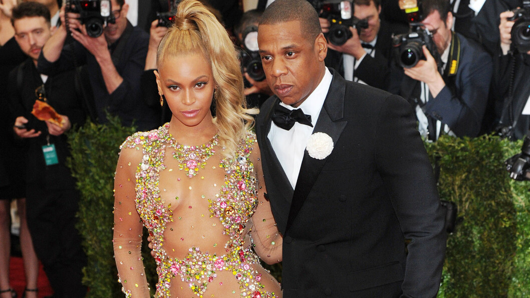 MYSTISK PIZZAMANN: Da Beyoncé og Jay Z lot seg fotografere, snek det seg en ukjent mann med en pizza i hånden bak dem. Foto: Broadimage