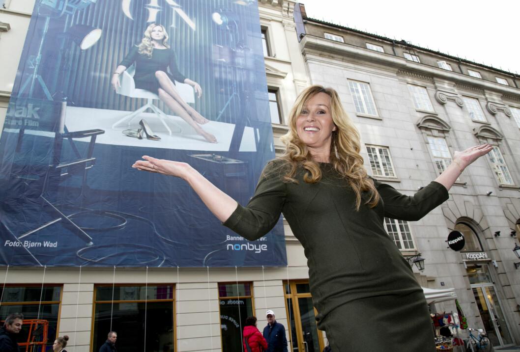 HOLDER KOKEN: Dorthe poserer foran den svære «God kveld Norge»-plakaten, som ble hengt opp ved TV 2 på Karl Johan i forbindelse med programmets nylansering tidligere i vår.  Foto: Se og Hør