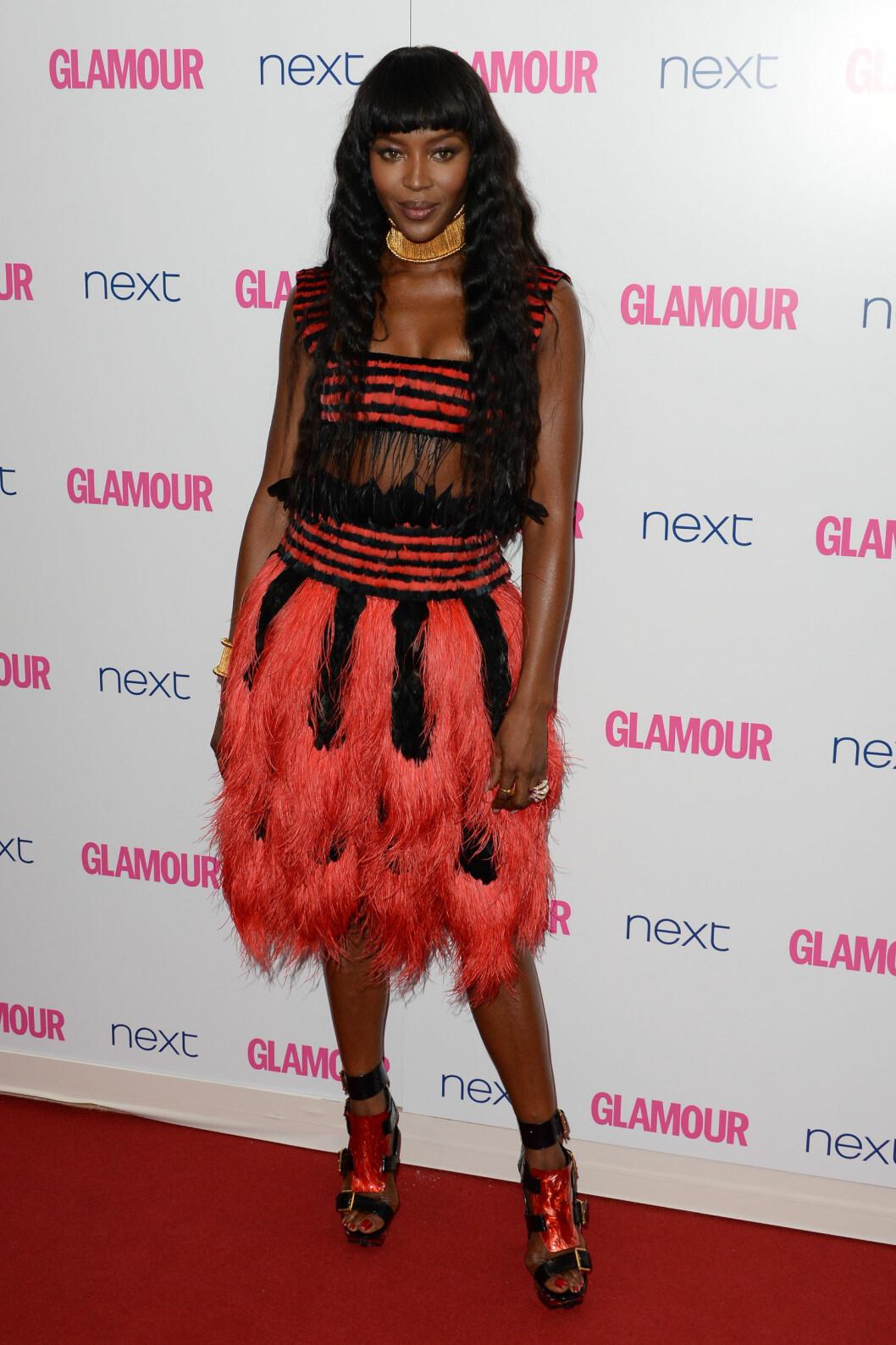 <strong>FJÆR:</strong> Naomi Campbells spesielle fjærkjole i rødt og sort, kombinert med voldsomme sko og smykker på Glamour Awards i juni, ble nok for mye for Seoghør.nos lesere - som trillet terningen til én. Foto: Stella Pictures