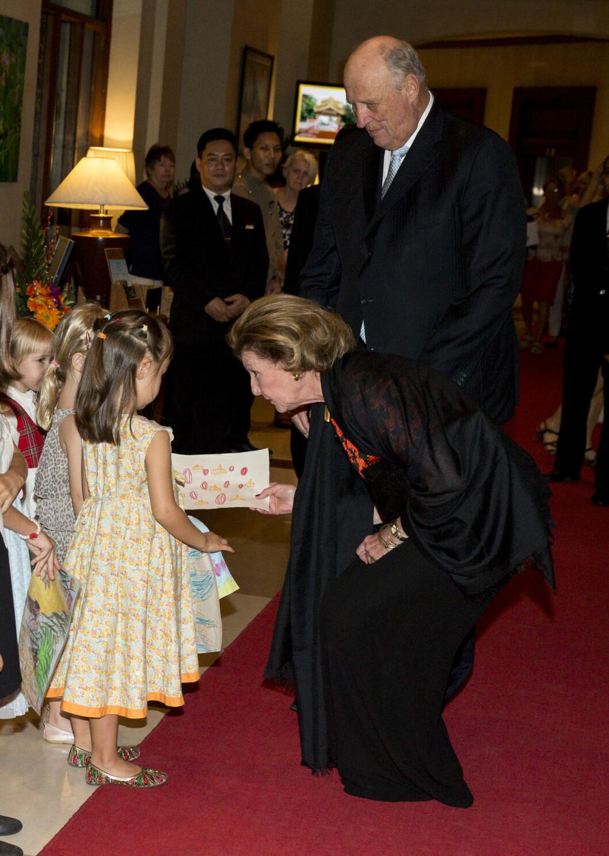 KONGELIG HILSEN: Det er ikke hver dag man får dronning Sonja til å knele for en, men da kongeparet møtte norske barn på Chatrium Hotel under statsbesøket Myanmar var det nettopp dét dronningen gjorde for å komme i nærkontakt med de små. Foto: Andreas Fadum