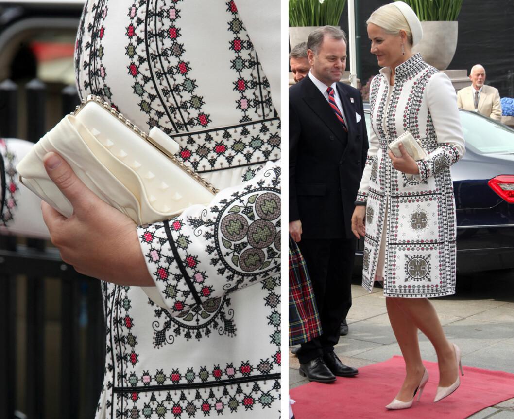 KORSSTING: Kronprinsessen var kledd i en folklore-inspirert kåpe dekorert med korssting da hun besøkte Stortinget torsdag denne uken. Kåpen fra Valentino var matchet med en plastveske fra samme merke.  Foto: FameFlynet