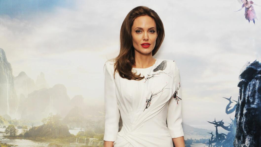 ET EVENTYRLIG SYN: Skuespiller Angelina Jolie sees vanligvis i sort både på og utenfor den røde løperen. Da hun fredag dukket opp i en snehvit, figursydd kjole på pressetreff i London, fikk hun derfor alle til å sperre opp øynene. Foto: Stella Pictures