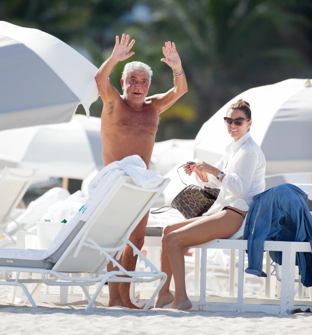 GODT HUMØR:  Roberto Cavalli og hans bikinikledde kjæreste Lina Nilson koste seg stort på stranda. Foto: All Over Press