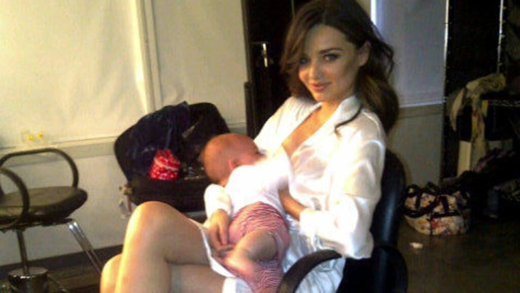 MODELL OG MAMMA: Miranda Kerr vet å kombinere rollene som supermodell og nybakt mamma. Her ammer hun like gjerne sønnen Flynn mens hun er på fotooppdrag. Foto: Twitter/ All Over Press