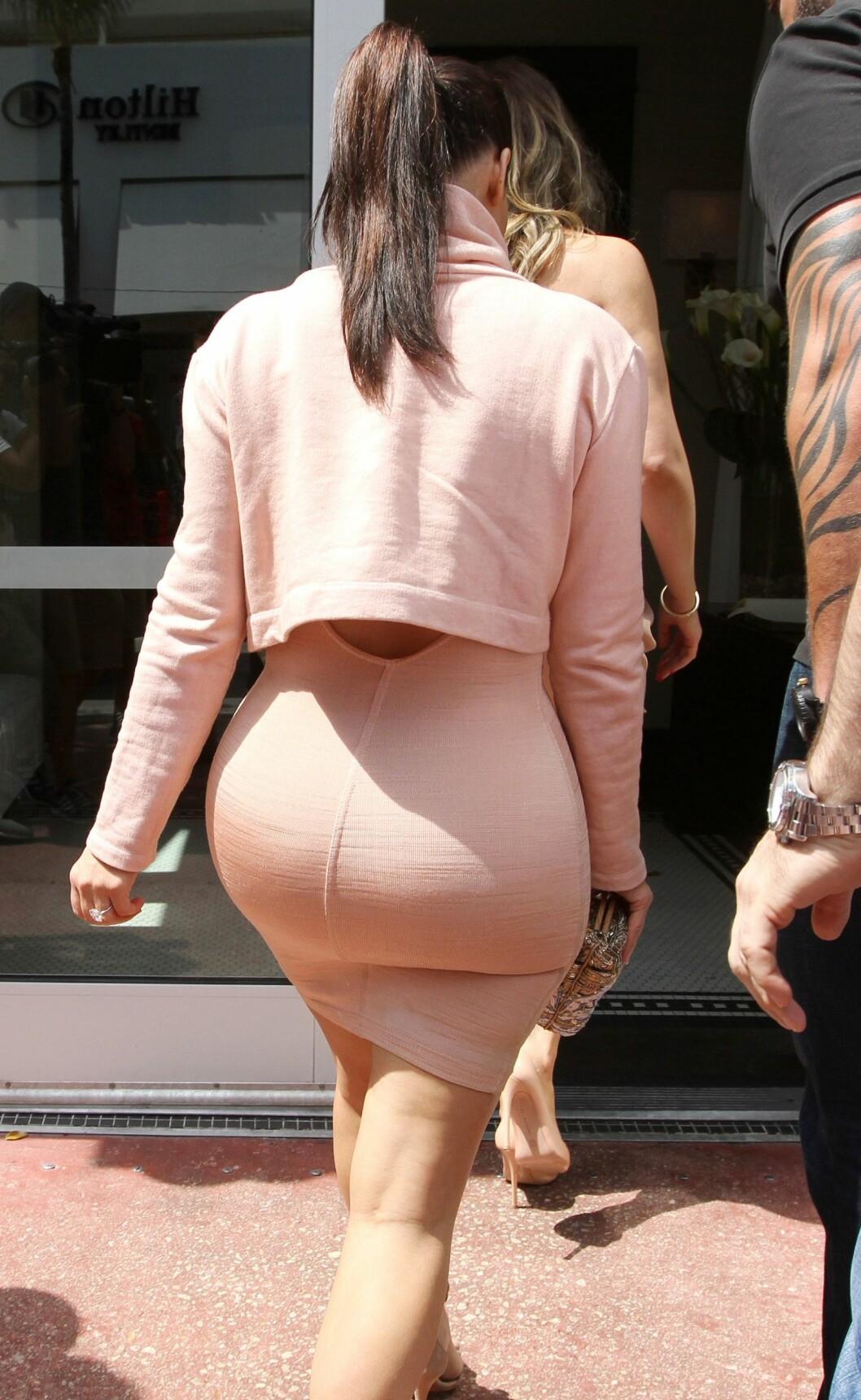 BERØMT BAK: Kim kardashians generøse stump vekket oppsikt i Miami onsdag ettermiddag. Realitystjernen var iført en åletrang pudderrosa kjole og matchende magetopp som viste frem hennes berømte figur.  Foto: REX/Broadimage/All Over Press