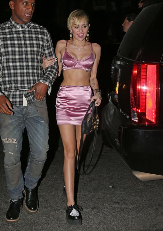 <strong>KOM I BH:</strong> Miley Cyrus ankom sin egen lanseringsfest i rosa BH og matchende miniskjørt. Foto: All Over Press