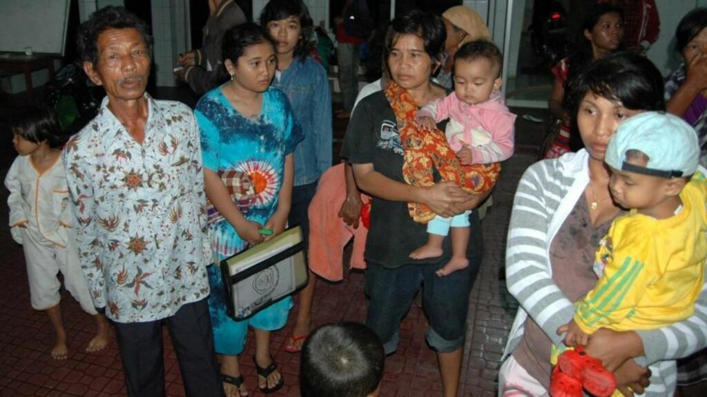SAMLET SEG ETTER TSUNAMIVARSEL : Indonesere samles utenfor hjemmene sine etter at et jordskjelv målt til 7,5 på Richters skala brøt ut rett vest for den indonesiske øya Sumatra i går kveld. Det ble sendt ut tsunamivarsler. Nå har flodbølgen rent innover øygruppene i vest.