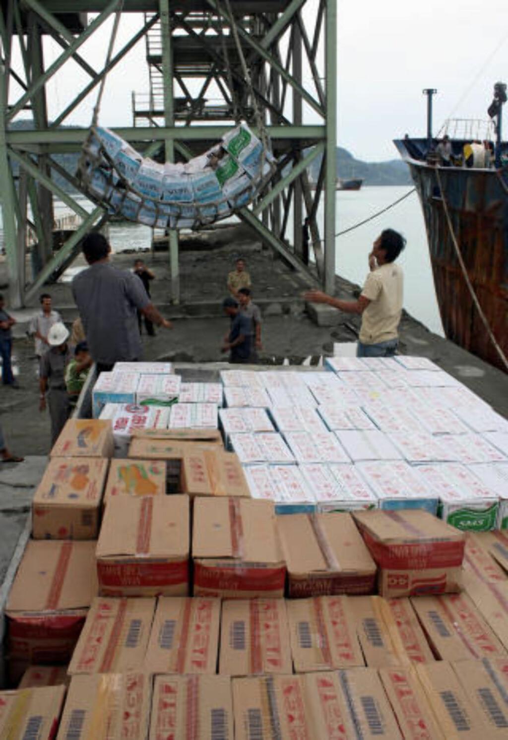 LESSER, MEN KOMMER IKKE FRAM : Lokale menn lesser nærmere 16 tonn med nødhjelpsrasjoner fra det lokale Disaster Management Agency til ofrene etter tsunamien og vulkanutbruddene. På grunn av dårlig vær er det vanskelig å få rasjonene fram. Foto: Rus Akbar/AFP.