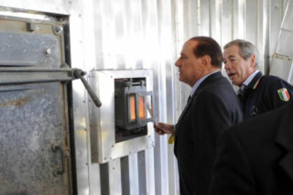 SER ETTER SØPPELLØSNING:  Italias statsminister Silvio Berlusconi får demonstrert en søppelforbrenningsovn i Napoli torsdag. FOTO: SALVATORE LAPORTA, AP/SCANPIX.