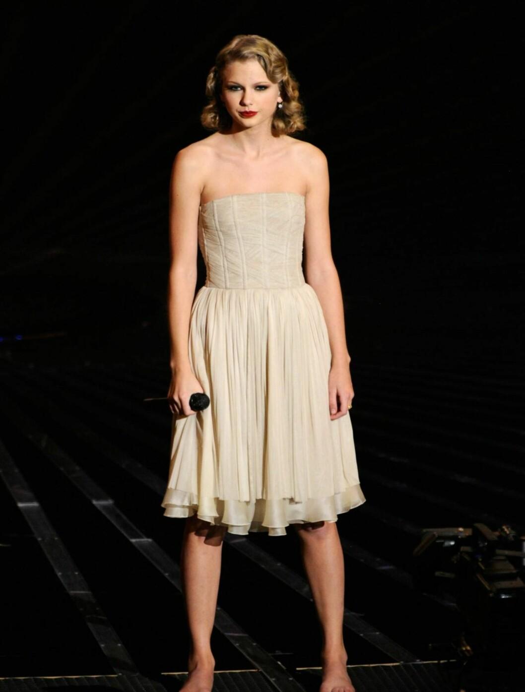 BEST: Popstjernen Taylor Swift så henrivende ut på scenen iført en lekker, elfenbensfarget Dolce & Gabbana-kjole. Foto: All Over Press