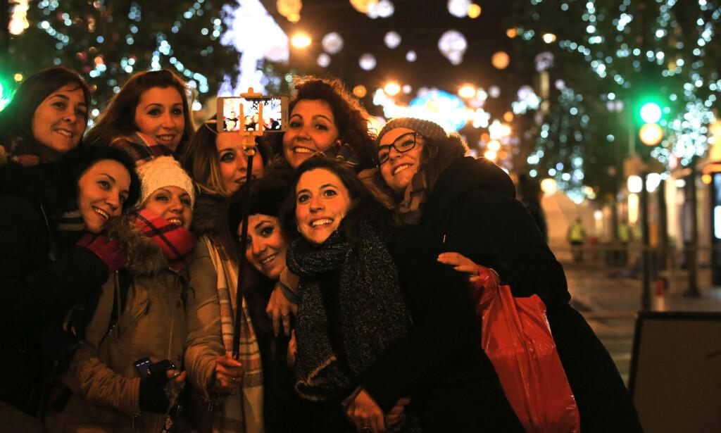 JULE-SELFIE: Tenningen av julegata i Oxford Street samler hvert år tusenvis av mennesker. Denne gjengen ville gjerne ha en gruppe-selfie. Foto: PA / NTB Scanpix