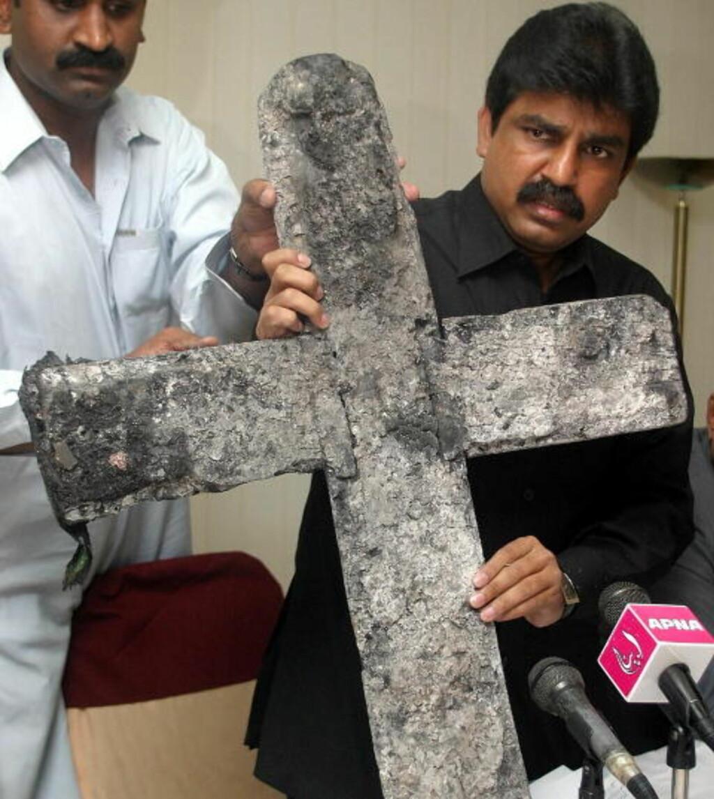 UTSATT: Minoritetsminister Shahbaz Bhatti med et utbrent kors etter at en kirke ble brent ned. Kristne er en utsatt minoritet i Pakistan. Foto: Reuters