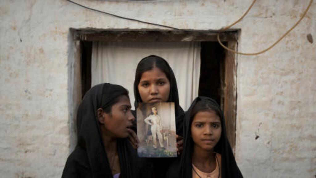 VIL HA MOR HJEM: Her er tre av døtrene til Asia Bibi. De viser frem et bilde av moren utenfor huset deres i Punjab-provinsen. Til venstre Esha (12), Sidra (18) and Eshum (10).  REUTERS/Adrees Latif