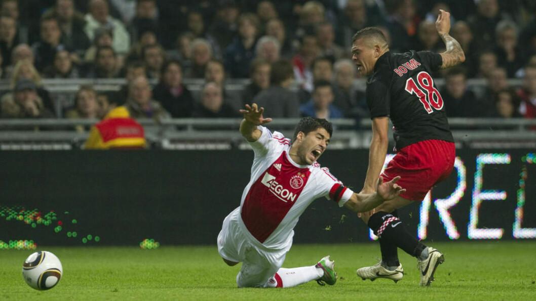 VAMPYR? Luis Suarez går i bakken i en duell med PSVs Wilfred Bouma under lørdagens kamp. Ajaz-kapteinen satte seinere tennene i skulderen til PSVs Otman Bakkal. Nå blir han straffet av sin egen klubb. Foto: Toussaint Kluiters, AFP/Scanpix