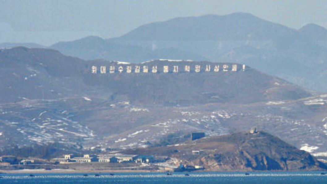 <strong>STRIDSSONE:</strong> Bildet viser Nord-Koreas vestkyst sett fra øya Yeonpyeong, som nå blir angrepet. På bildet ser man artilleribunkere, og et skilt som lyder Lenge leve Den store leder Kim Il-Sung. Foto. AFP PHOTO/KIM JAE-HWAN