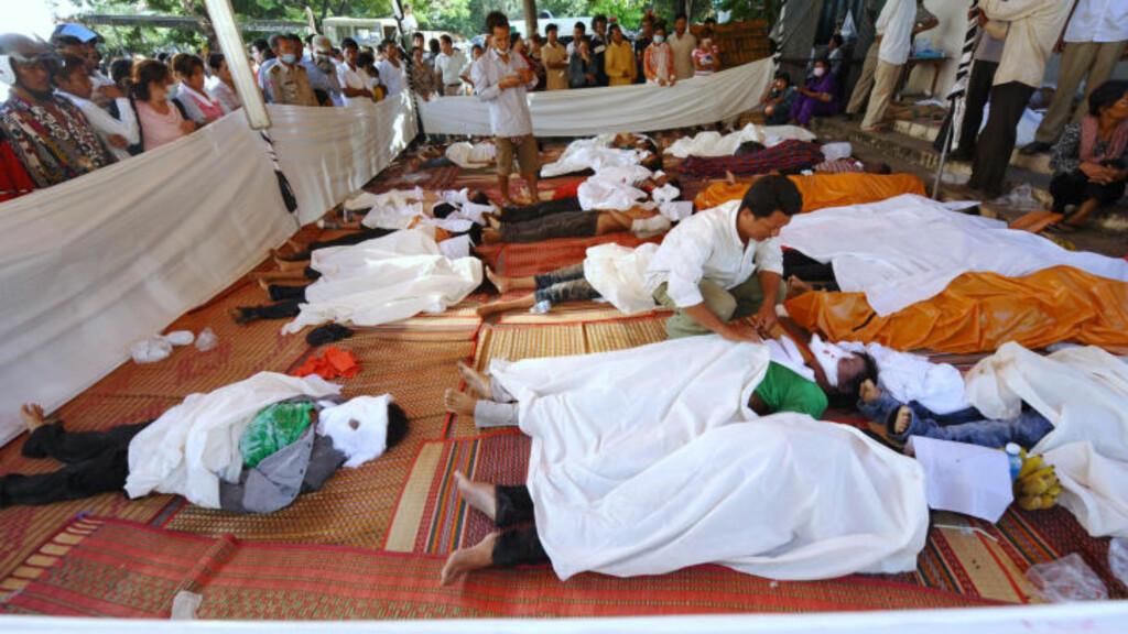 LIKESKUE:  Pårørende leter etter sine kjære. Her er døde etter vannfest-tragedien lagt til skue utenfor et sykehus i Phnom Penh tirsdag. FOTO: HOANG DINH Nam, AFP/SCANPIX.