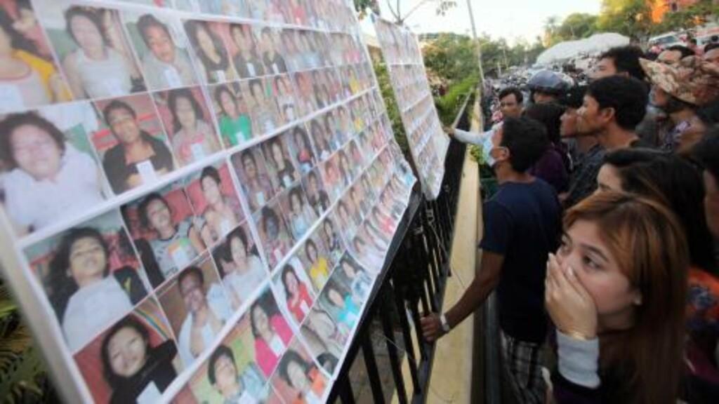 SJEKKER DØDE:  Pårørende som savner venner eller familie sjekker bilder av døde som er hengt opp på gata i Phnom Penh. FOTO: MAK REMISSA, AFP/SCANPIX.