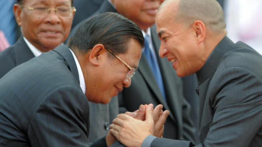 FØR TRAGEDIEN:  Kong Norodom Sihamoni (til høyre) hilser på  statsminister Hun Sen under åpningen av vannfestivalen lørdag. Nå sammenligner statsministeren festtragedien med folkemordet under Pol Pot. FOTO: TANG CHHIN SOTHY, AFP/SCANPIX.