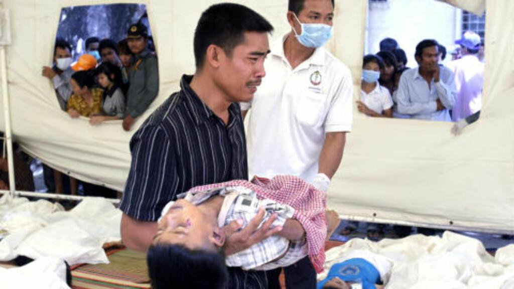 FANT SØNNEN:  En kambodsjansk far gråter med sin døde sønn i armenene etter å ha funnet gutten blant de døde på Kossamak-sykehuset i Phnom Penh. FOTO: SAKHAI LALIT, AP/SCANPIX.