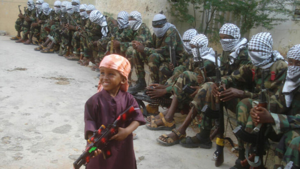 OPPRØRERE: Her holder en somalisk gutt et lekevåpen foran al-Shabaab-krigere i Mogadishu. Vold og krig er hverdagen til sivile i Somalia. Foto: AFP Photo/Aburashid Abikar/Scanpix