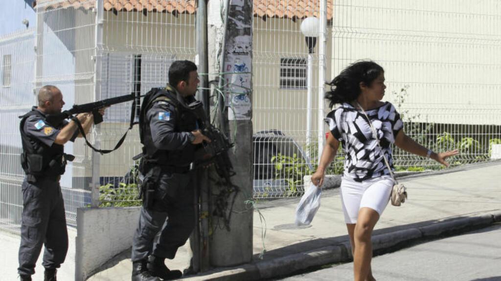 URBANE STRØK: En innbygger i Rio de Janeiro løper i tilflukt under politiaksjonen. Foto: Reuters/Sergio Moraes/Scanpix