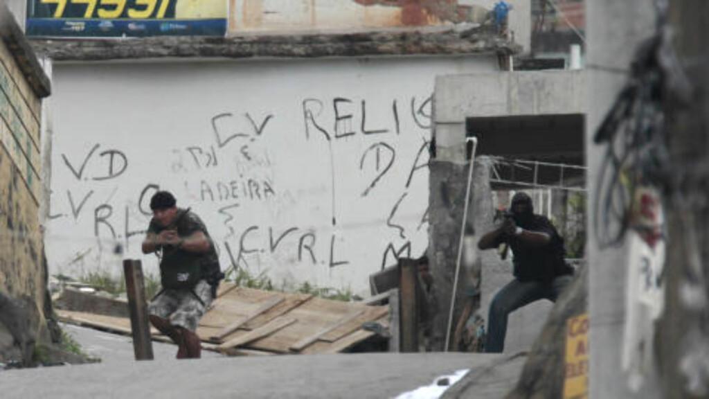SKUDDVEKSLING: Her sikter angivelige gjengmedlemmer våpnene mot politiet under en politiaksjon i Rio de Janeiro. Foto: AP Photo/Silvia Izquierdo/Scanpix
