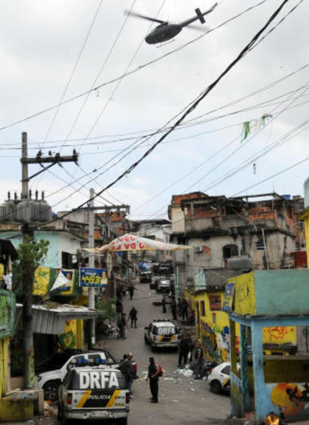 TAR KONTROLL: Politihelikopteret svever i lufta over Vila Cruzeiro-slummen mens politiet tar kontroll over området. Foto: AFP Photo/Evaristo Sa/Scanpix