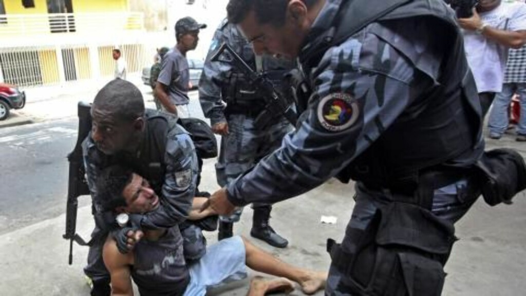 HARDHENDTE: Politiet kontrollerer en mann etter en hendelse på en bar i området politiet aksjonerte i dag. Foto: AP Photo/Silvia Izquierdo/Scanpix