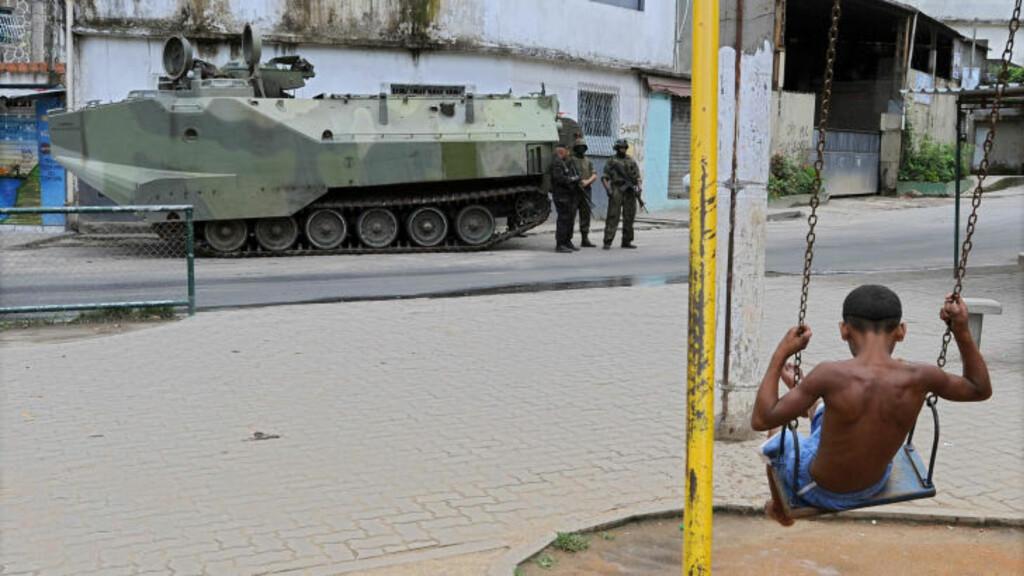 RULLET INN MED STRIDSVOGN: Et barn leker mens soldater patruljerer gatene i Vila Cruzeiro-slummen i Rio de Janeiro. Foto: AFP Photo/Evaristo Sa/Scanpix