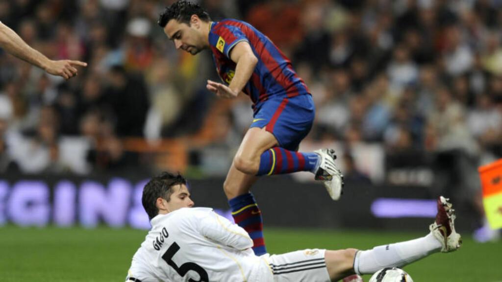 PASNINGSMESTEREN: Xavi har ikke mye til overs for Mourinhos fotballsyn. Her i duell med Gago under et av forrige sesongs møter med Real Madrid. Foto:  AFP PHOTO/Dani POZO .