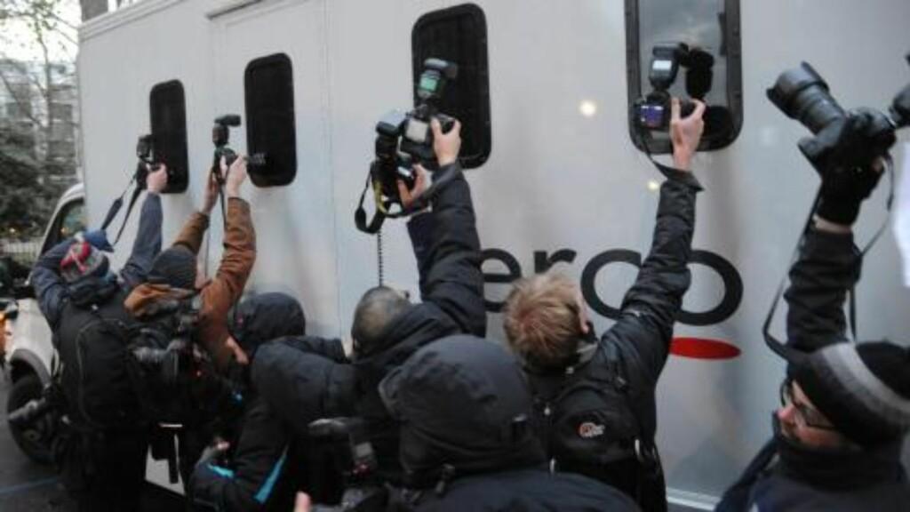 FENGSLET: Fotografer prøver å ta bilde gjennom vinduene til en fangebuss som angivelig skal være den som transporterte Wikileaks-grunnlegger Julian Assange til fengsel. Foto: EPA/Andrew Gombert/Scanpix