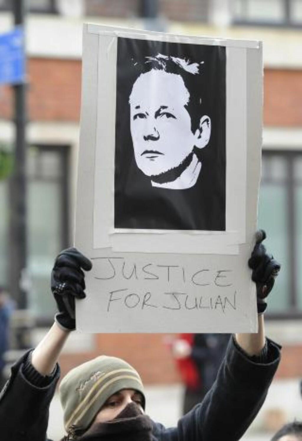 """DEMONSTRERTE: En demonstrant holder en plakat med bilde av Julian Assange og teksten """"Justice for Julian"""" - """"Rettferdighet for Julian"""". Foto: EPA/Facundo Arrizabalaga/Scanpix"""