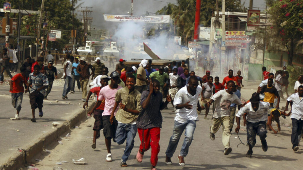 LØPER FRA TÅREGASS:  Folk løper fra tåregass som ble avfyrt av FN-soldater i Port-au-Prince. Andre sa at FN-soldatene knapt var å se under opptøyene. Foto: REUTERS / St-Felix Evens / SCANPIX