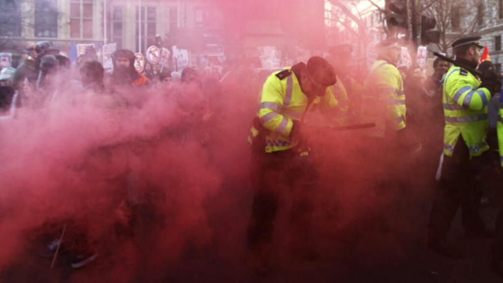 RØYKLAGT: Rød røyk er blant virkemidlene som blir brukt under sammenstøtene i Westminster. Foto: Stefan Wermuth/Reuters/Scanpix