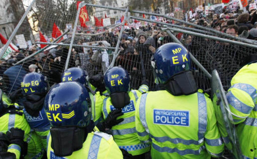 REV NED BARRIKADENE: Demonstrantene lot seg ikke stoppe av barrikadene som var satt opp på området. Bak sperringene sto hjelmkledde politifolk klare. Foto: Stefan Wermuth/Reuters/Scanpix