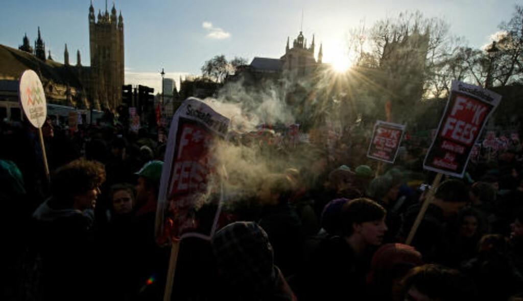 BRENNER PLAKATER OG AVGIFTER:  Studentdemonstraner brenner plakater utenfor Parlamentet i London i dag, torsdag, i protest mot regjeringens foreslåtte tredoble økning av studieavgifter. Foto: Leon Neal/AFP/Scanpix