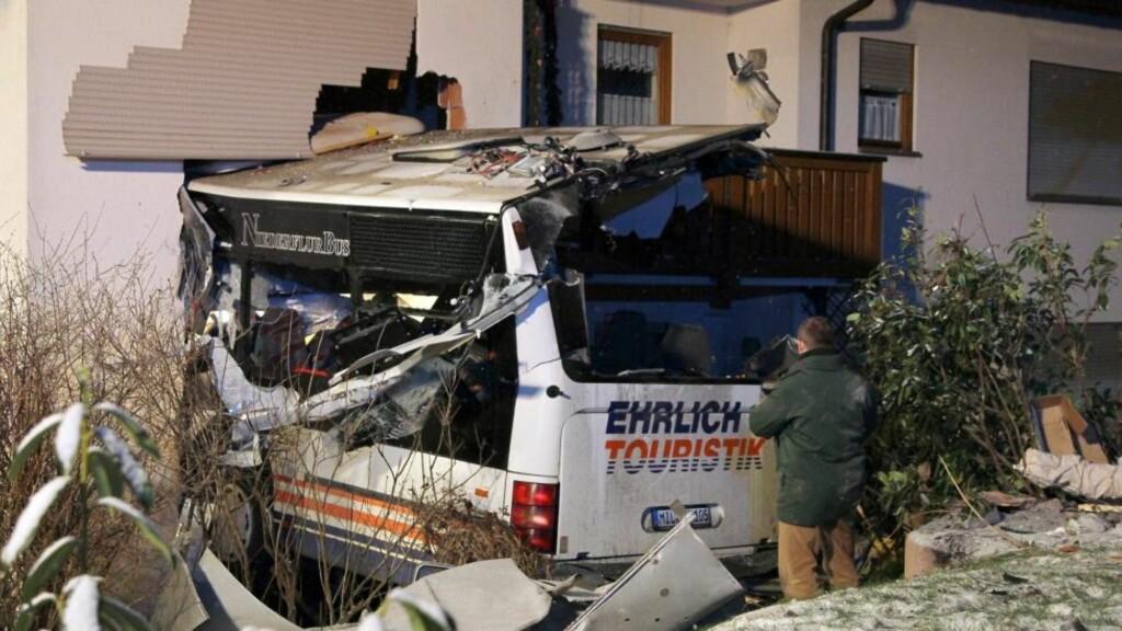 TO DØDE: En passasjer og bussjåføren omkom da bussen skled av veien og kjørte inn i en leilighet i Miltenberg i Tyskland. Foto: EPA/RALFHETTLER/SCANPIX
