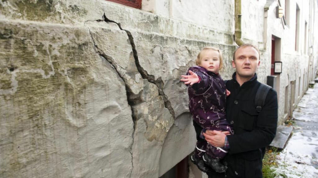 STORE SPREKKER: Heine Askeland (35) og datteren Mia (2) viser fram store sprekker i grunnmuren og fundamentet til bygården i Ladegårdsgaten i Bergen. FOTO: Marit Hommedal / Scanpix