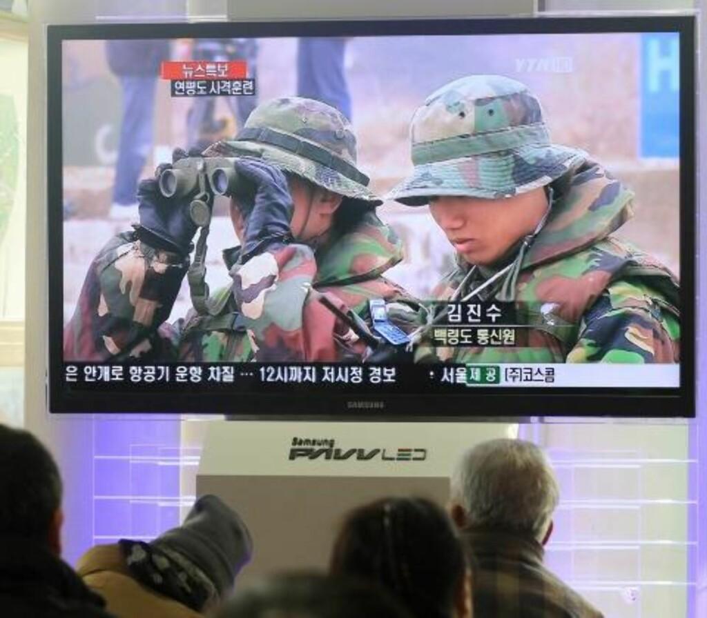 FØLGER MED: Innbyggere i den sørkoreanske hovedstaden Seoul følger bilder angivelig fra øvelsen vist på sørkoreansk tv. Fire personer ble drept da Nord-Korea den 23. november avfyrte artilleriild på øya Yeonpyeong. Foto: EPA/YONHAP/SCANPIX