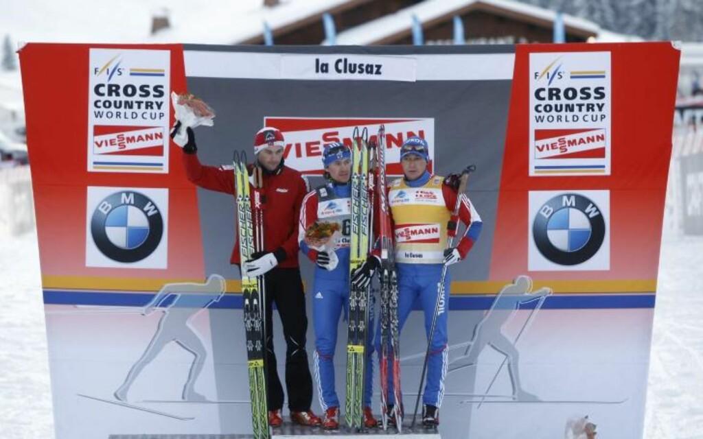 KOM SEG PÅ PALLEN TIL SLUTT: I ureglementert antrekk, kom Petter Northug seg til slutt opp på seierspallen sammen med Maxim Vylegsjanin (midten) og Aleksander Legkov.Foto: SCANPIX/AP Photo/Laurent Cipriani