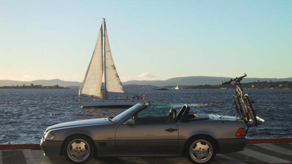 SØLV UTSTRÅLER VELSTAND: Her en eldre Mercedes, sølv metallic kabriolet, 1990-modell, i sommersol ved fjorden. Foto: GEIR BØLSTAD