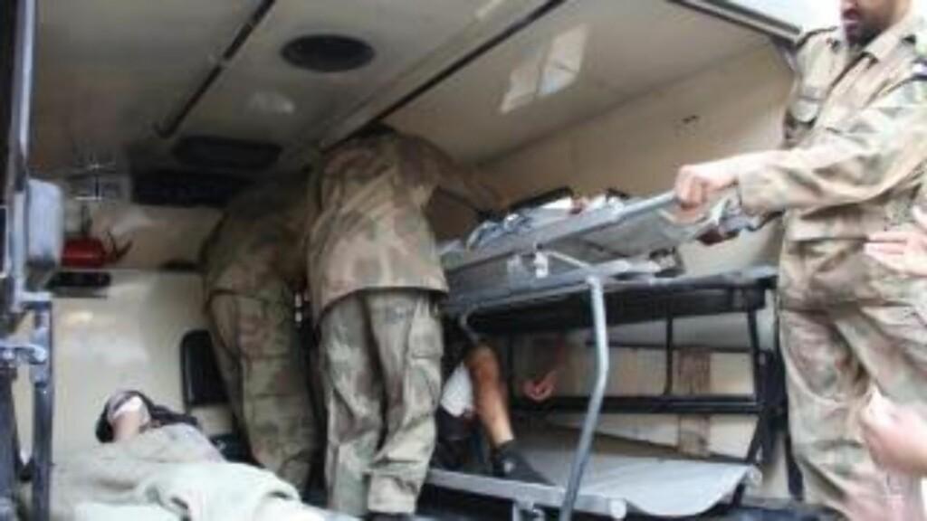 EVAKUERES: Militært ambulansepersonell frakter bort døde og sårede i Bajur-regionen første juledag.  EPA/ARSHAD ARBAB