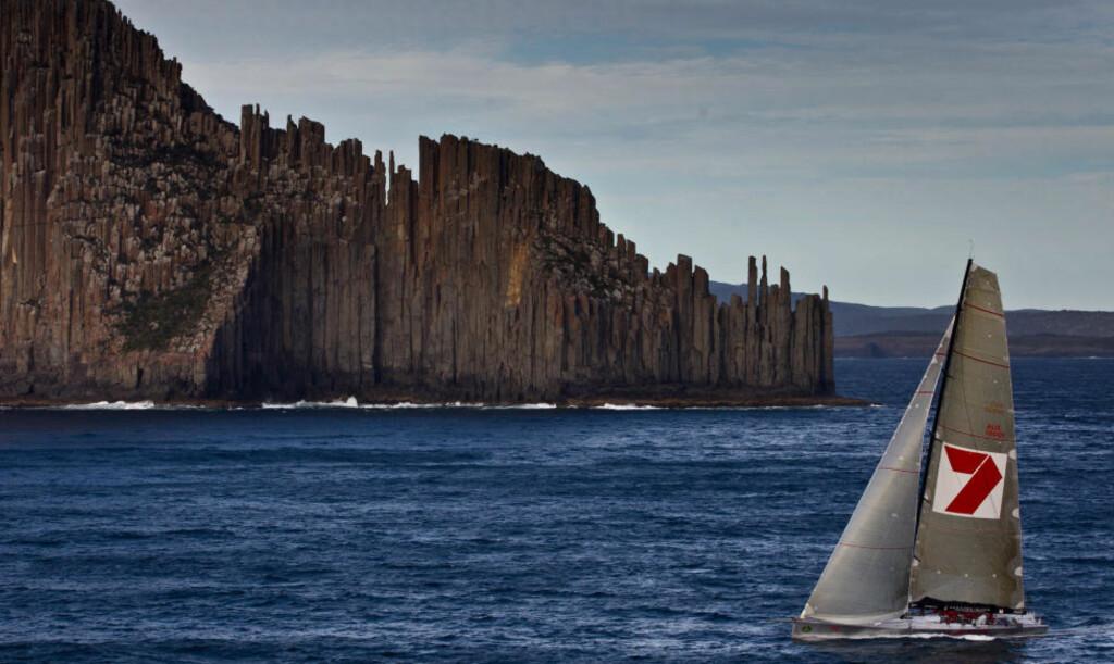 TILDELT SEIEREN: Wild Oats XI er bekreftet som vinner av seilasen fra Sydney til Hobart. Her passerer båten de karakteristiske «orgelpipene» ved Tasmania-kysten.Foto: SCANPIX / AFP PHOTO / HO / ROLEX / Daniel FORSTER